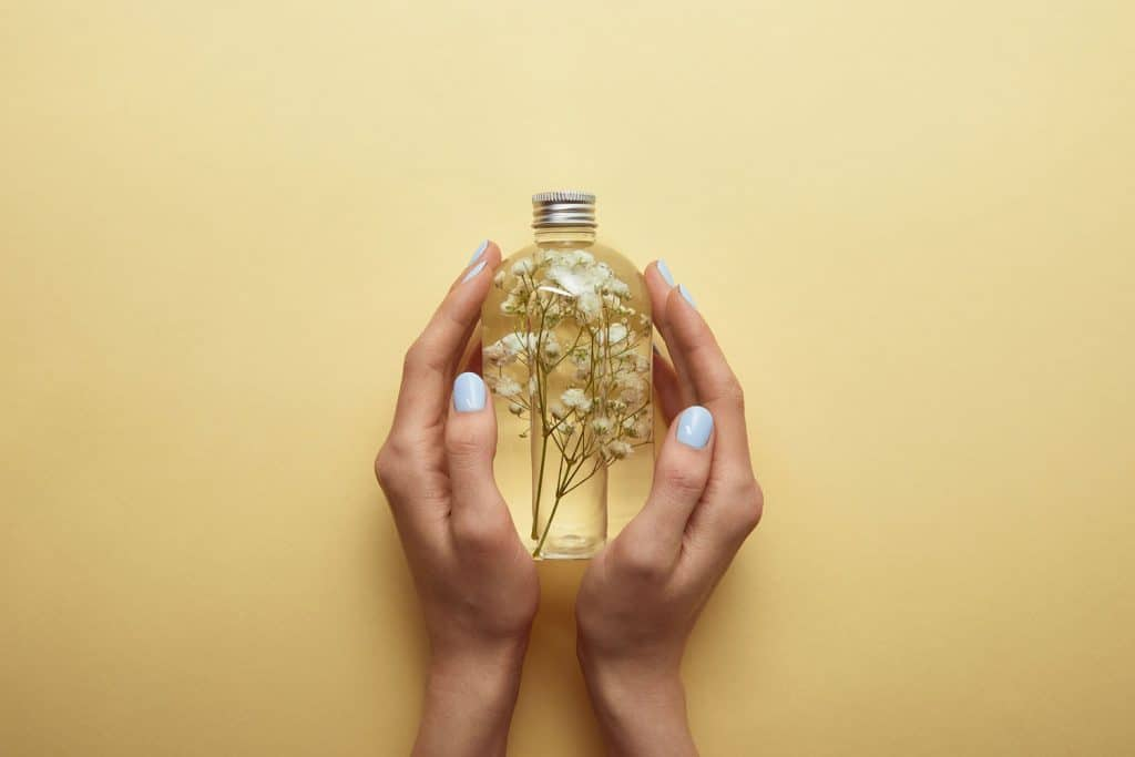 Partial view of woman holding bottle with natural beauty product and herbs in hands on yellow background