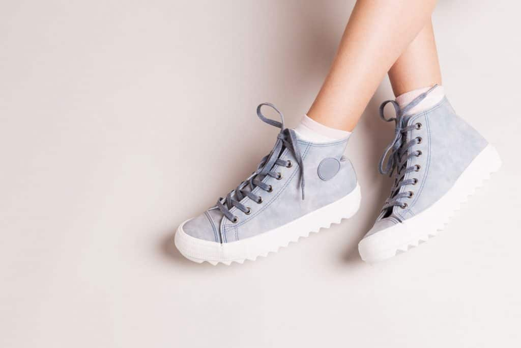 Pastel blue sneakers on crossed legs. Footwear on grey background