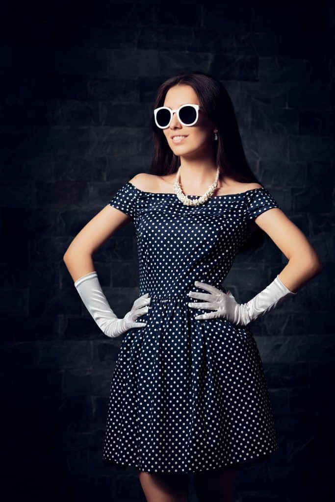 Retro fashionable girl wearing 50's inspired navy blue dress and jewelries