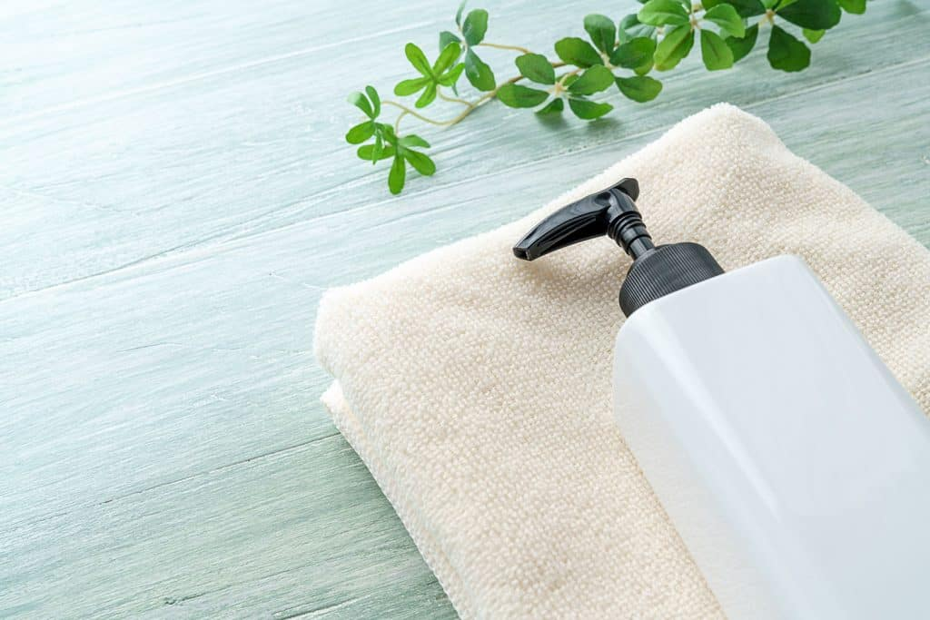 Shower gel bottle and towel on wooden background , below a plant stem with leaves