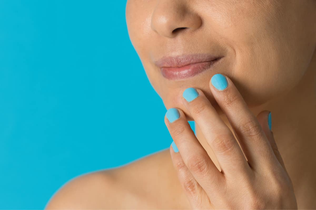 Smiling woman with blue polish on the blue background