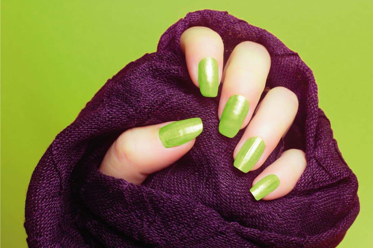 Female hand with neon green nails wearing a purple fabric on green background
