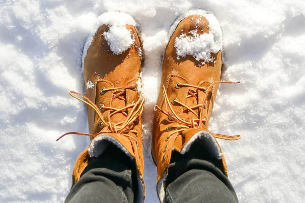 Top view of brown leather boots in fresh snow, What Shoes to Wear in Snow?