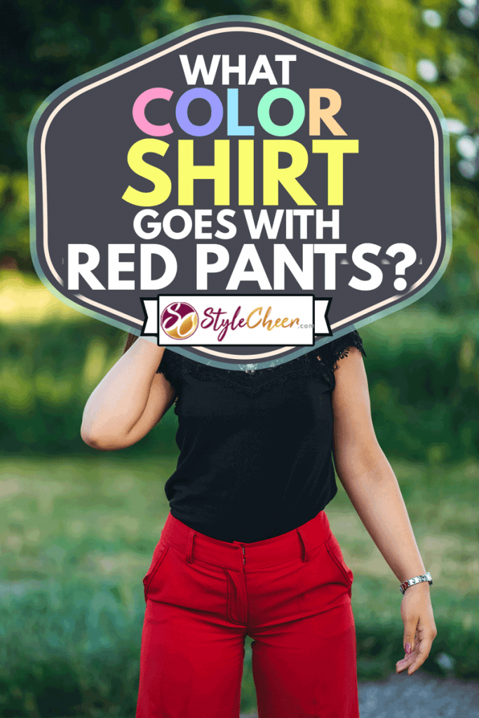 Pretty young caucasian woman posing in public park wearing red pants and black shirt, What Color Shirt Goes With Red Pants?