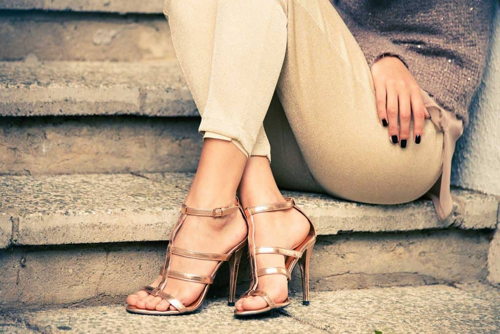 Woman in high heels sitting on stairs