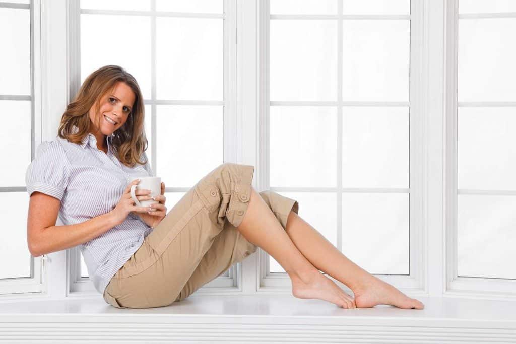 Woman sitting in a bay window, drinking coffee wearing khaki capris