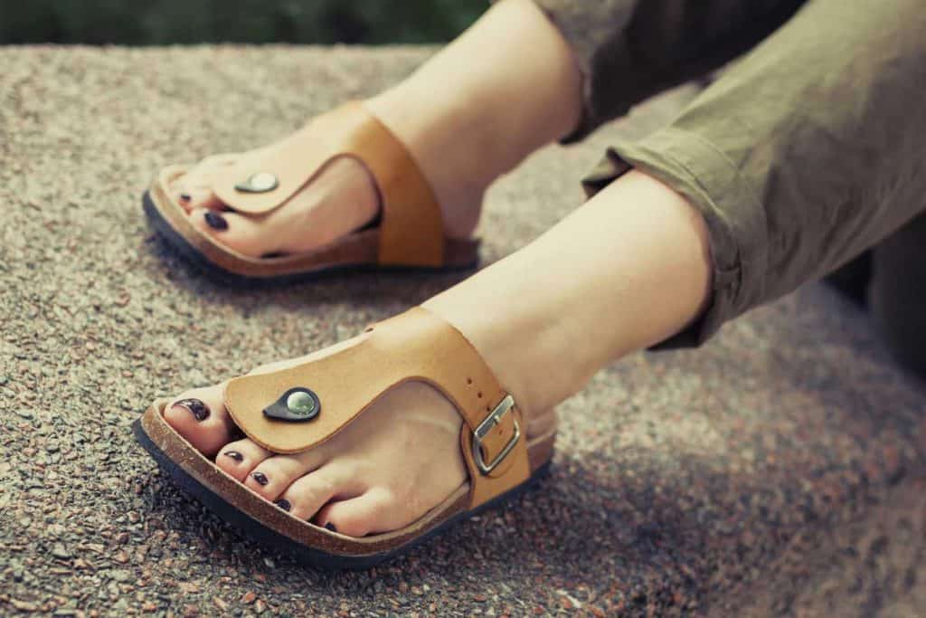 Woman's feet in yellow stylish summer sandals with dark nail polish, Should Sandals Be A Size Bigger?