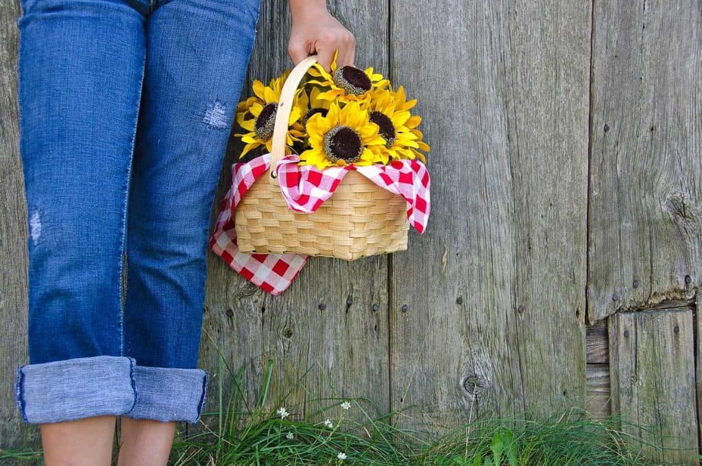 Young girl in blue jeans with basket of sunflowers