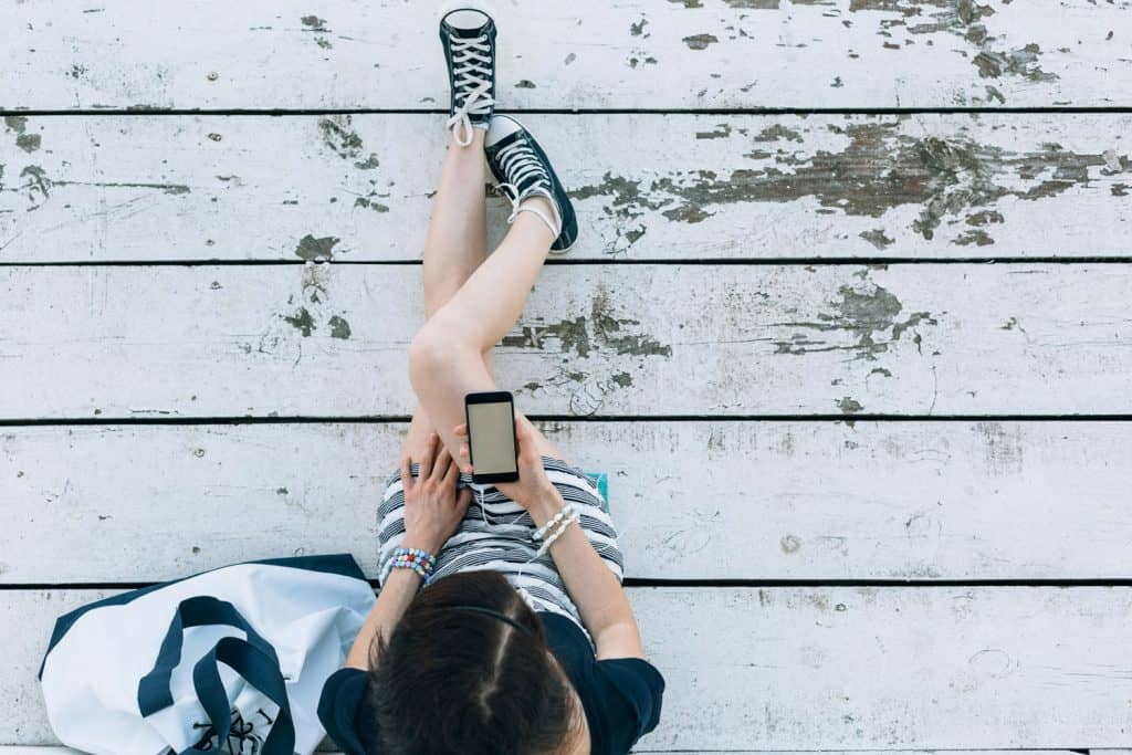Young girl sitting at wooden planks and using smartphone, What Color Sneakers Goes With Everything?