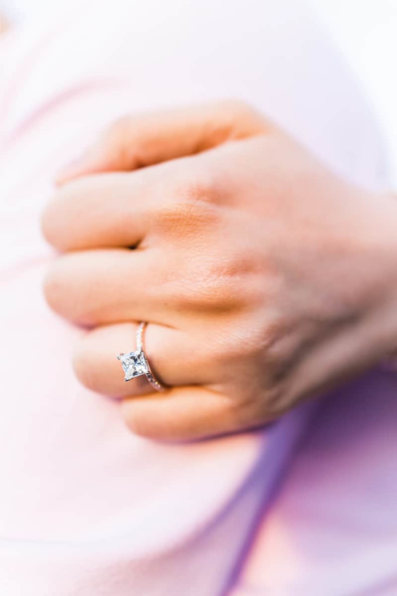 Young woman's hand with diamond engagement ring in princess cut