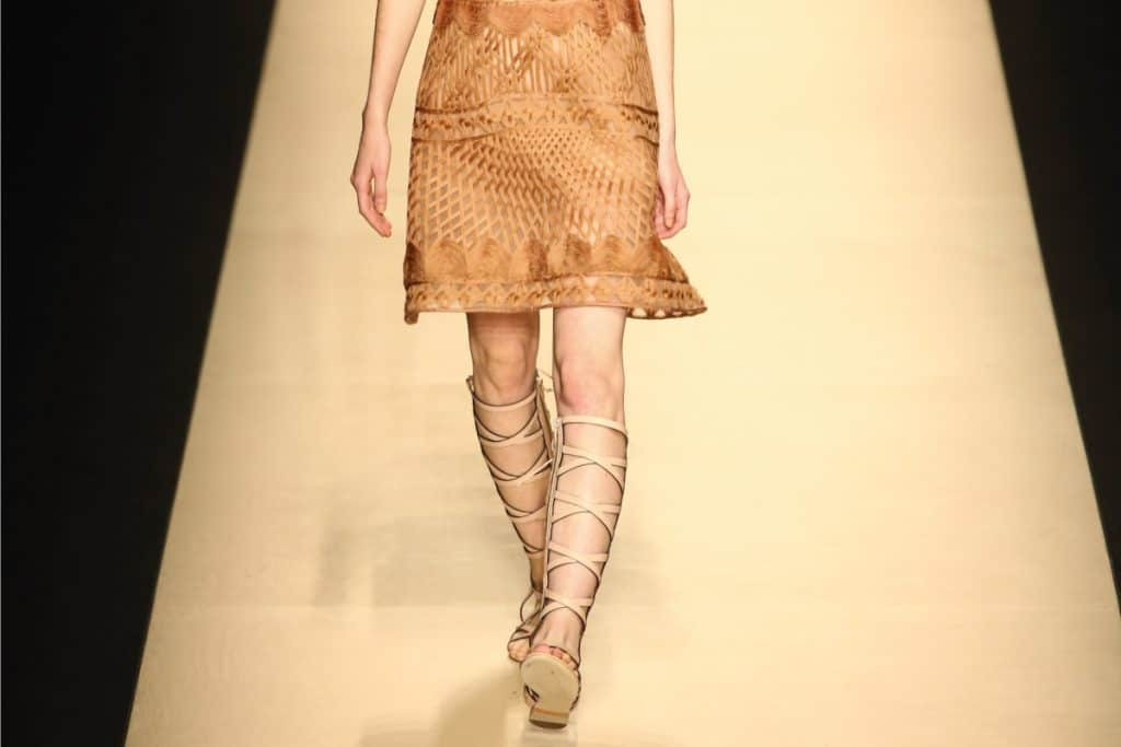 Close up photo of model wearing gladiator sandals while walking on a runway, What To Wear With Gladiator Sandals?