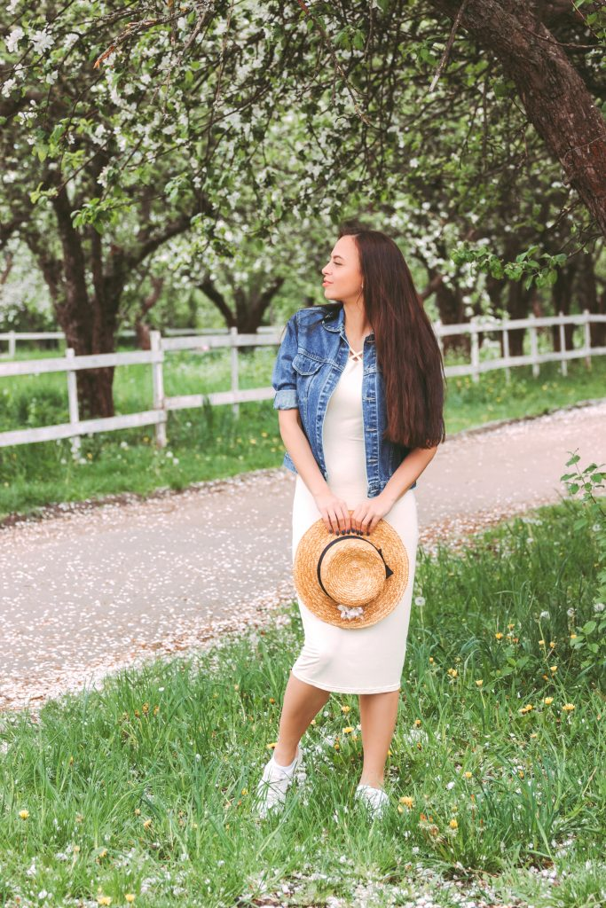 Stylish happy brunette hipster woman in denim jacket and stylish white dress posing on green countryside garden.