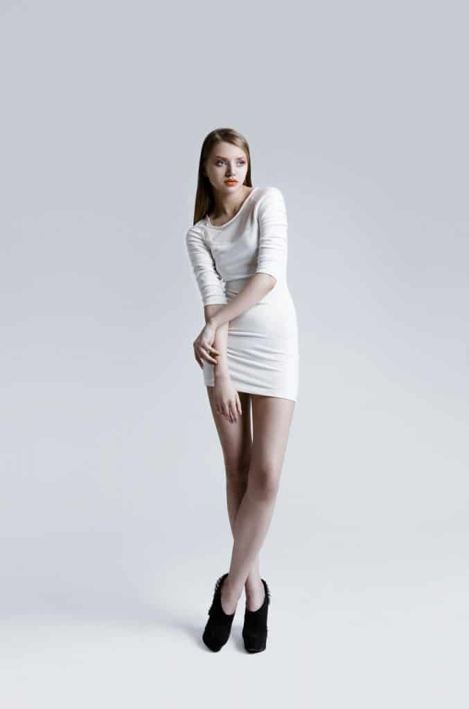 Attractive young slim woman with perfect professional make-up and simple hairstyle, wearing beautiful white dress and high heels black shoes