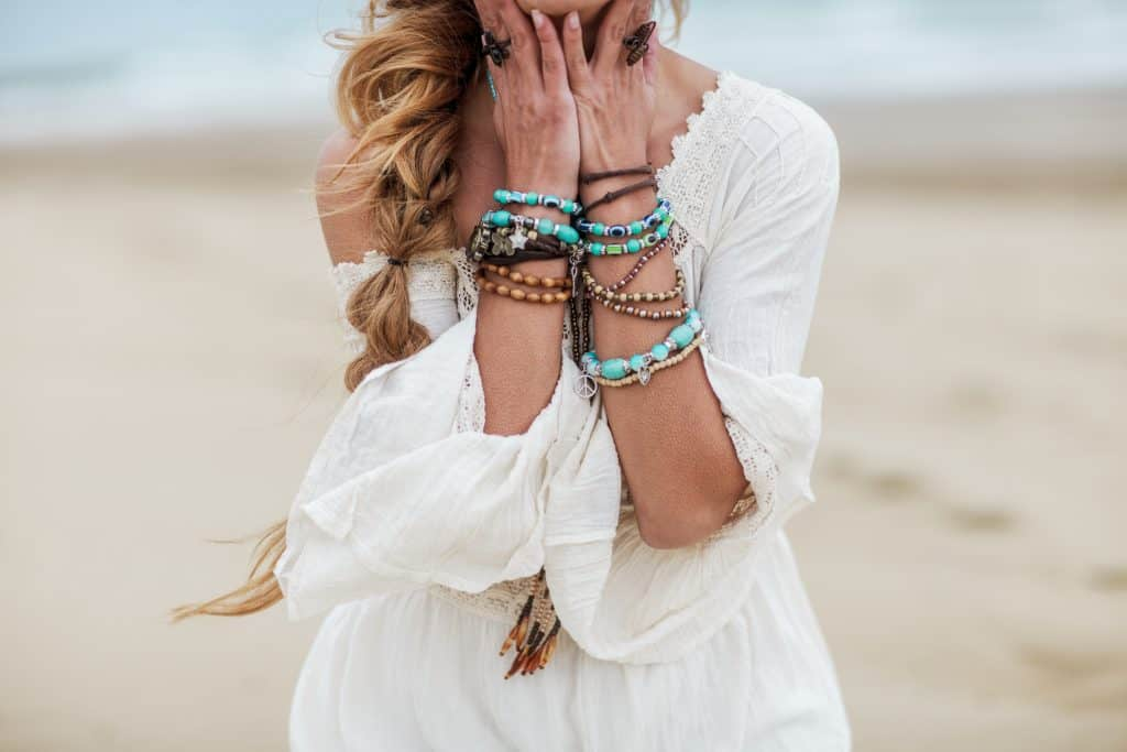 Boho woman wearing white dress with multicolored jewelry