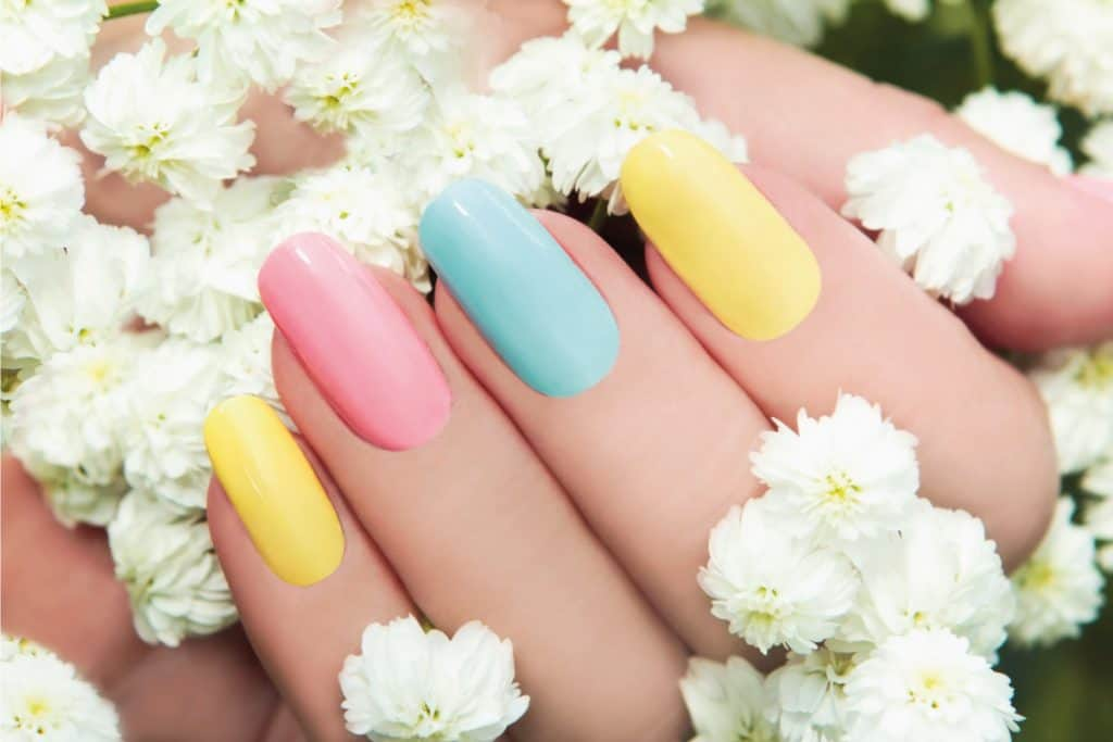 Pastel nail manicure on a woman's hand holding flowers, What Color Nails With Blue Dress [8 Awesome Suggestions]