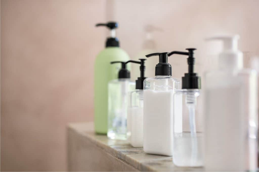 Shower gels in dispenser bottles stacked on a marble counter, Does Shower Gel Expire (Even When Unopened)