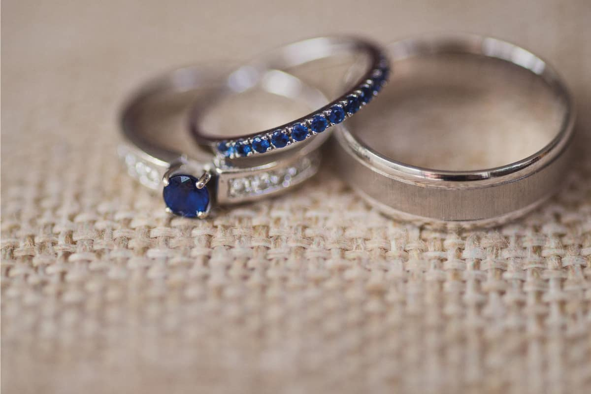 Wedding rings and engagement ring with blue gemstones on natural linen background