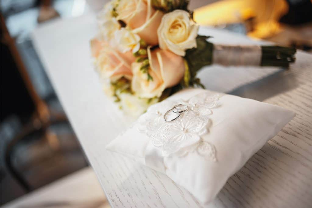 Wedding rings on a pillow cushion with bouquet at the back, Can You Wear An Anniversary Band As A Wedding Band?