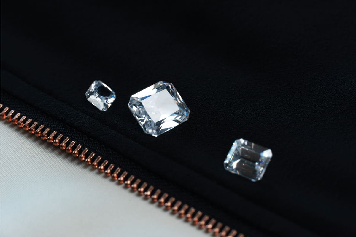White diamond or gemstone in emerald cut on black fabric with zipper