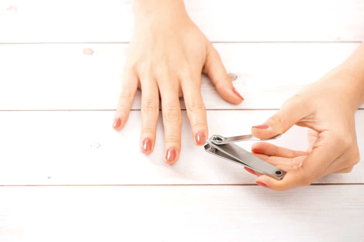 woman about to cut fingernails using nail clipper