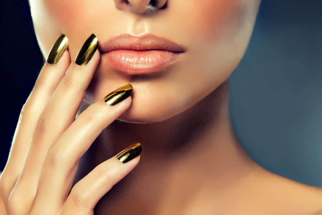 A beautiful woman showing her metallic golden acrylic nails