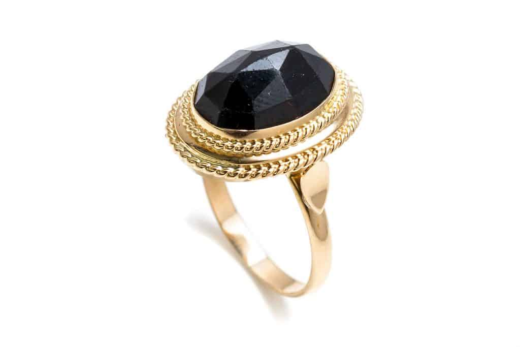 A gold ring with an onyx on the center placed on a white background