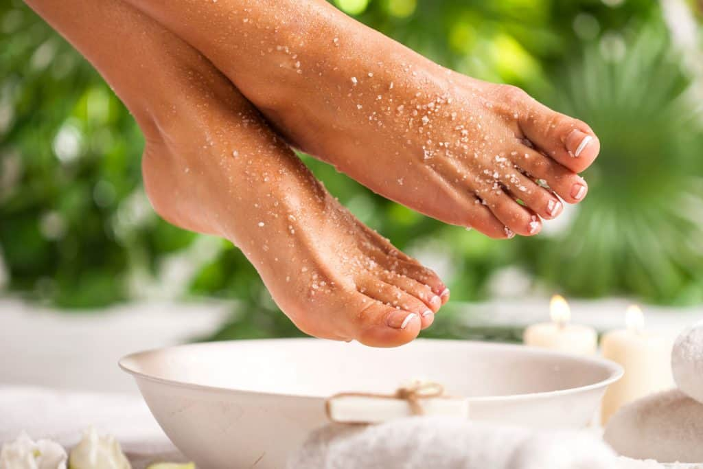 A woman exfoliating skin on a foot spa