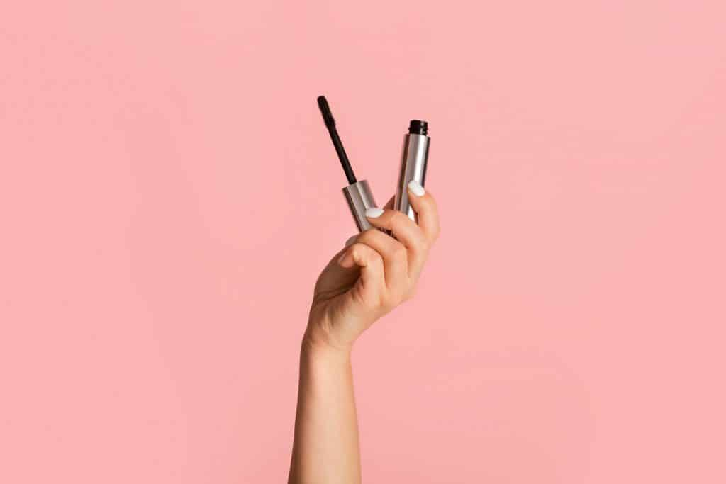 A woman holding her mascara on a pink background