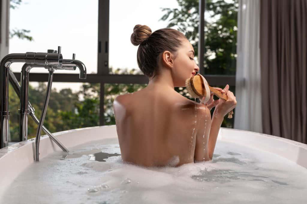 A woman on a bathtub using a scrub on her back, Should You Use Body Scrub Every Day?