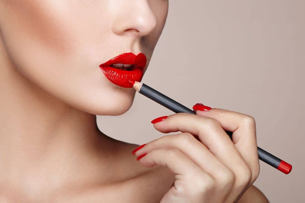 A woman putting a red colored lip liner on her lips for a photoshoot, Can Lip Liner Be Used As Eyeliner?