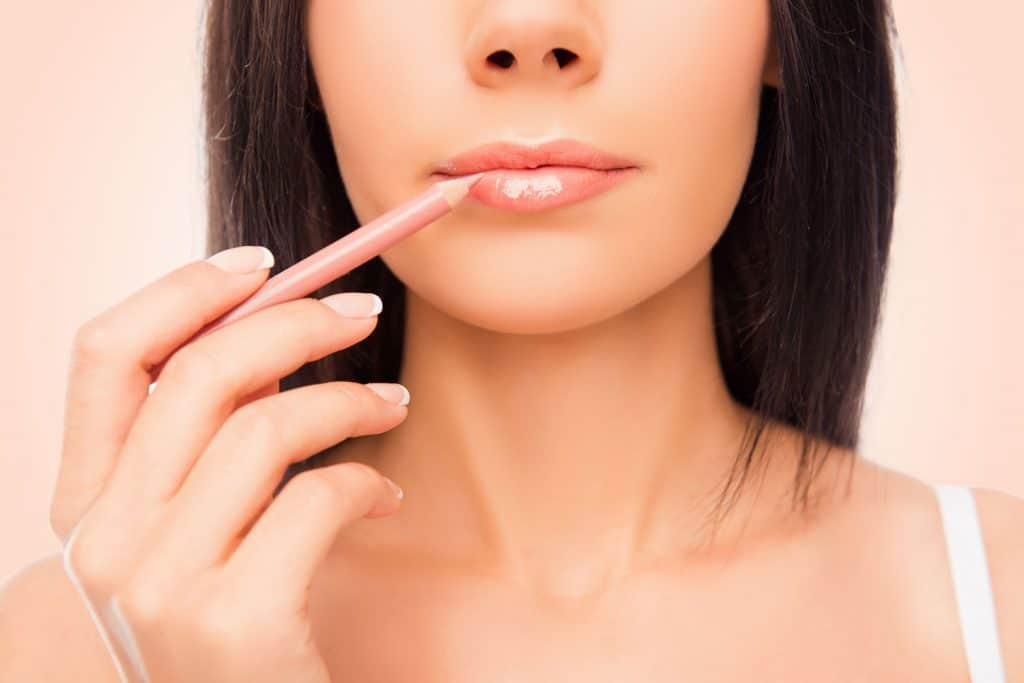 A woman putting on a pink colored lip liner, What Can I Use Instead Of Lip Liner? [9 Lip Liner Alternatives]