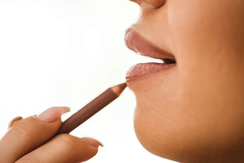 A woman putting on brown lip liner