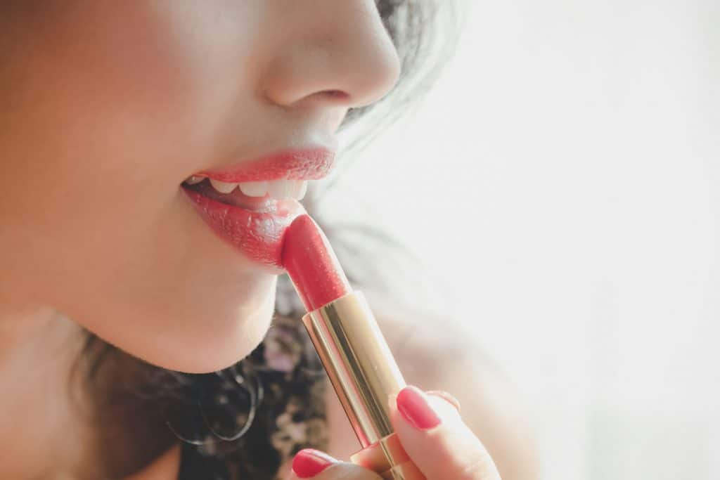 A woman putting on lipstick for a formal event