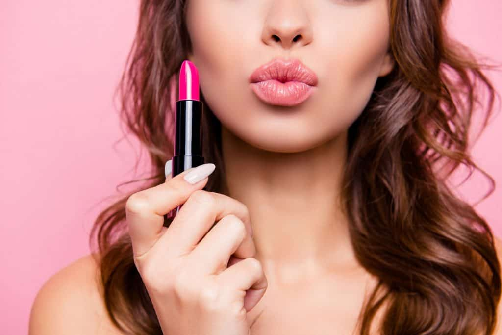 A woman showing her pink gloss lips and holding a pink lip gloss on a pink background, How To Use Lip Liner With Lip Gloss