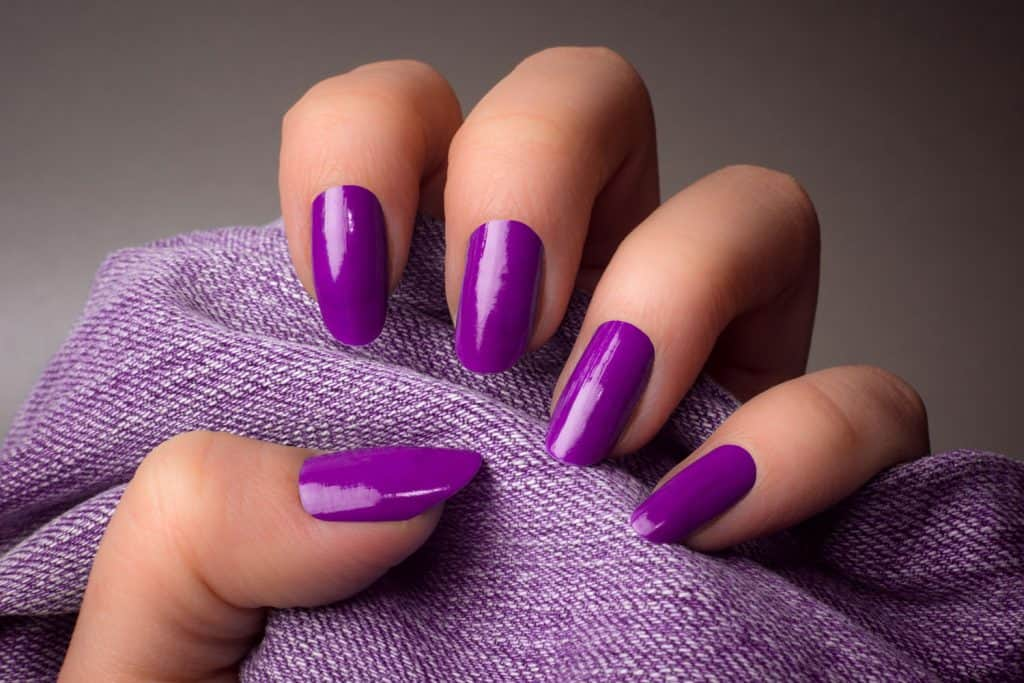 A woman showing her violet colored vinyl nail polish, How To Change Acrylic Nail Color [5 Steps]