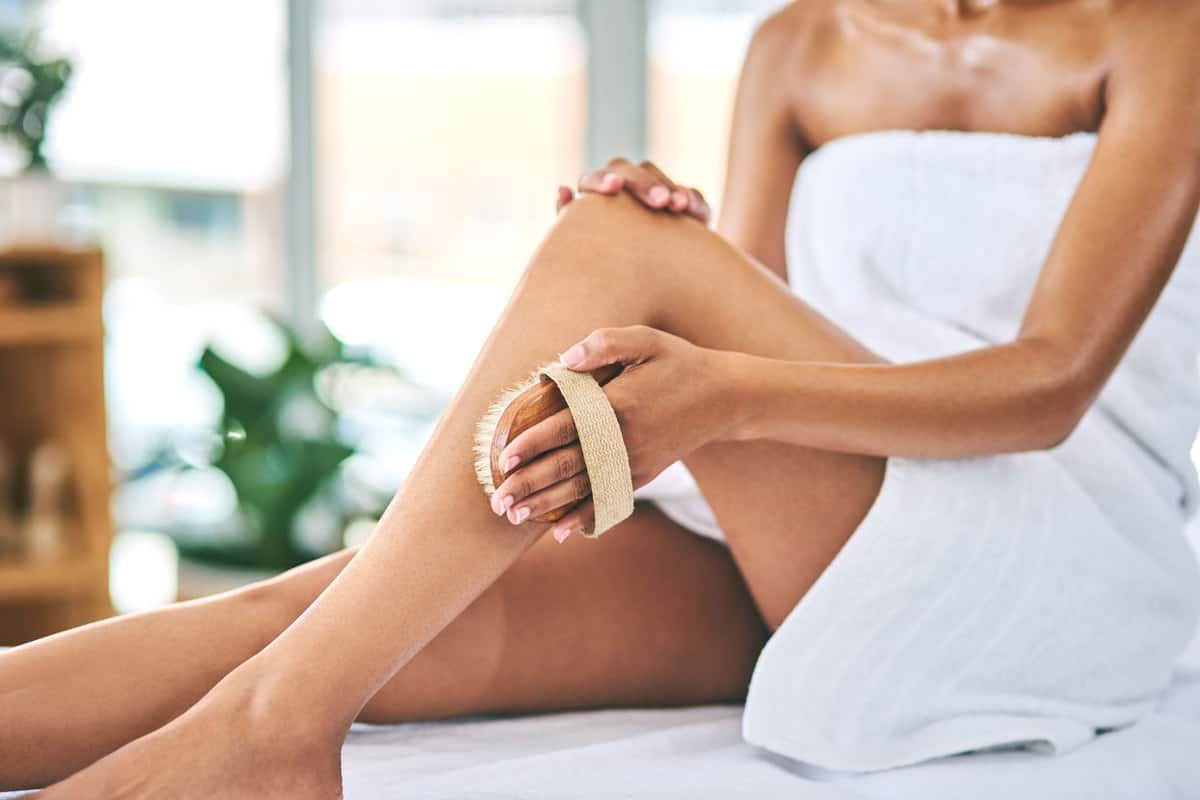 A woman using a body scrub on her legs after taking a shower