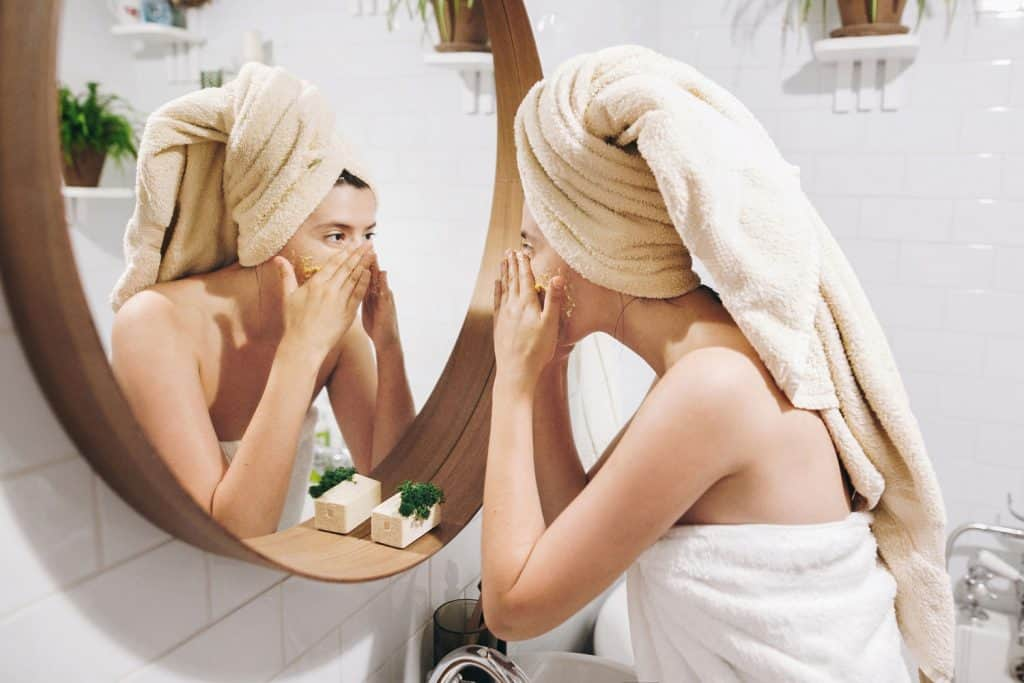 A woman using exfoliating cream on her face while staring at the mirrro