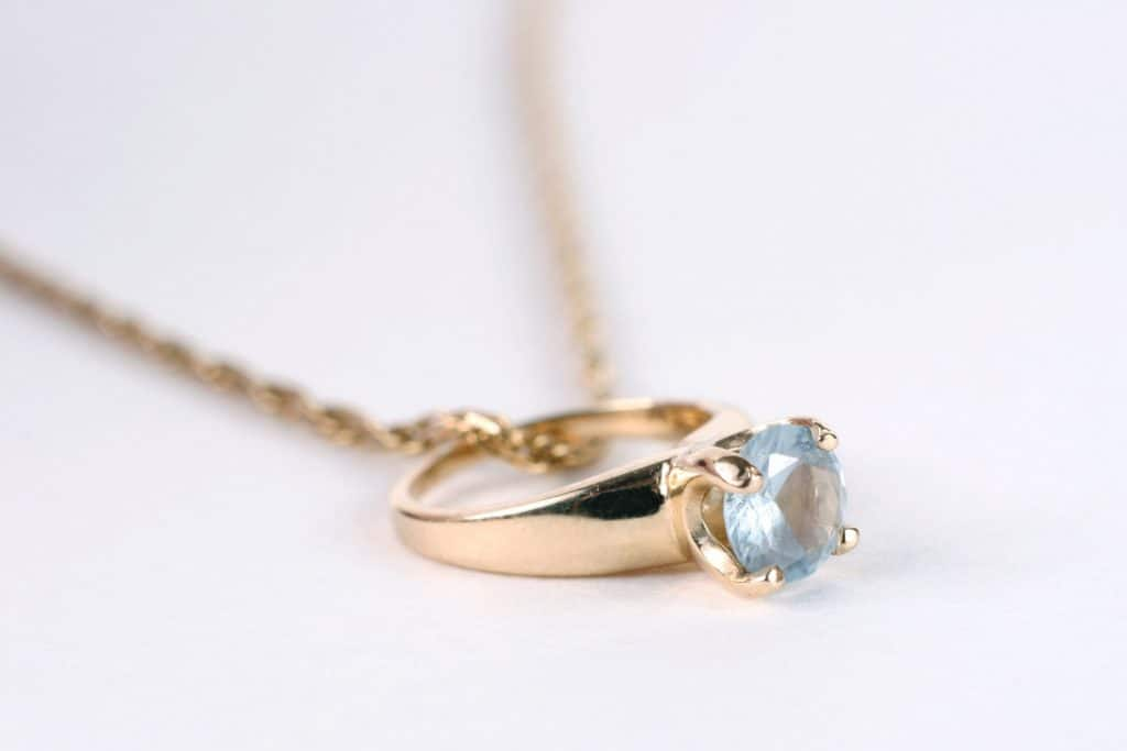 An aquamarine birthstone ring on a gold chain. Shallow depth of field.