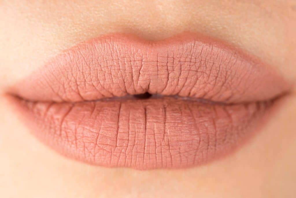 An up close and detailed photo of a woman putting on pink lipstick