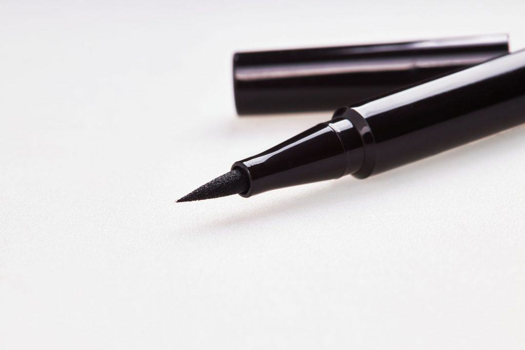 An up close photo of a black cosmetic eyeliner on a white background