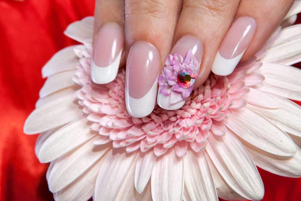 Beautiful manicured nails on a flower