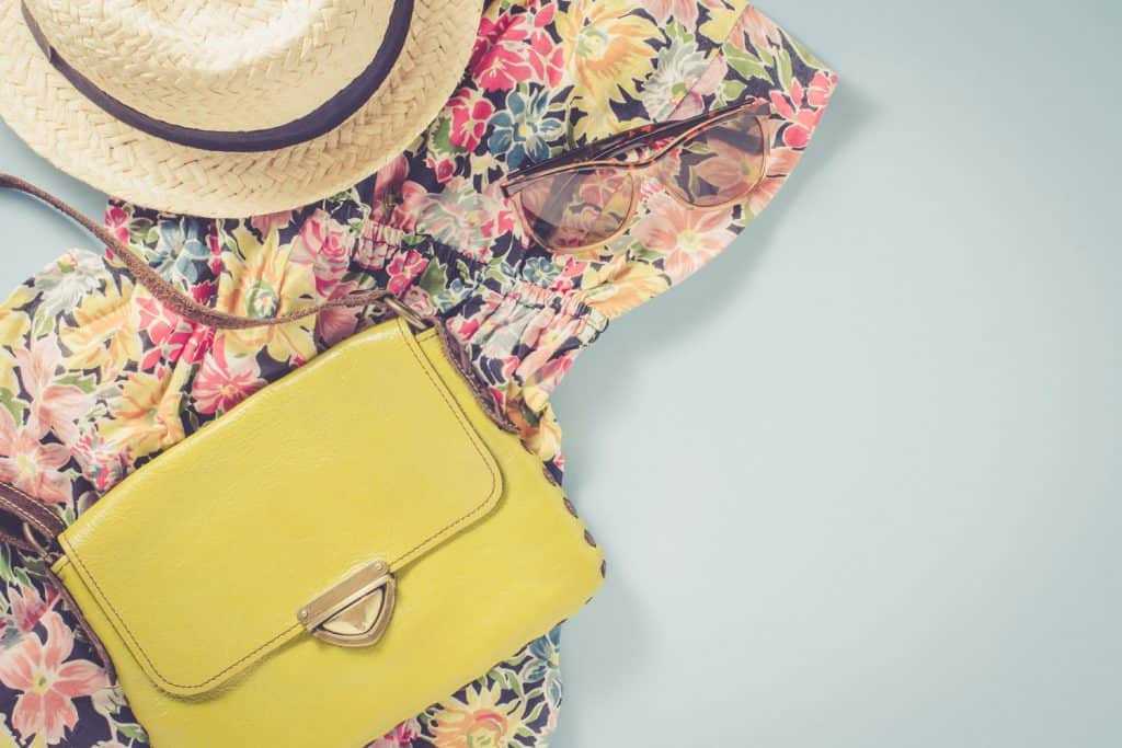 Casual female clothes over blue background with yellow handbag