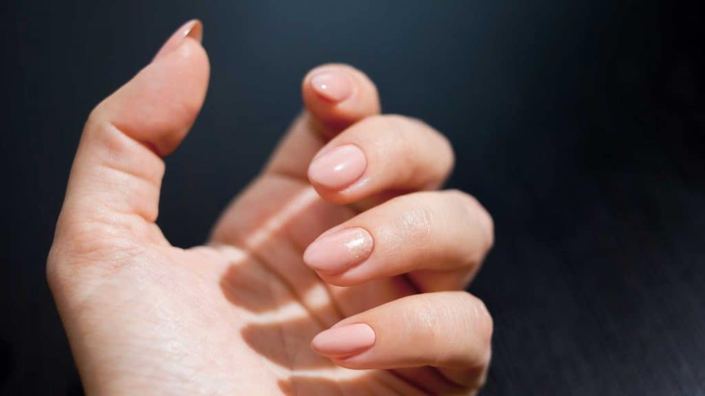 Close up hand of a woman with nude manicure with gold decor
