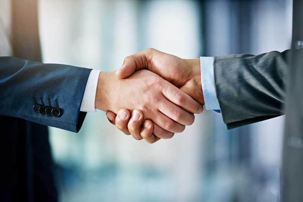 Close up shot of two businessmen shaking hands in an office