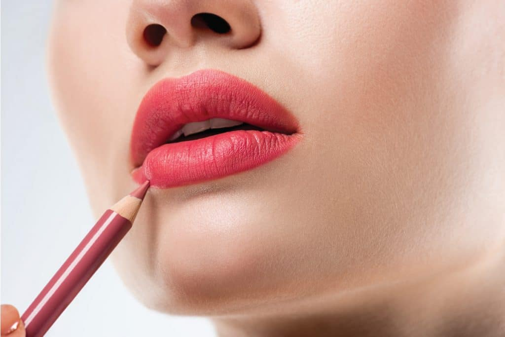Close up studio shot of woman applying lip pencil. How To Sharpen Plastic Lip Liner