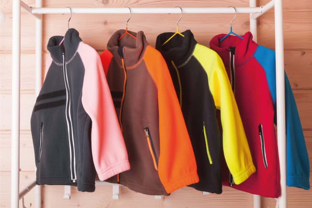 Colorful fleece jackets are hanging on hangers near wooden wall in a rack. 9 Types Of Fleece You Should Know