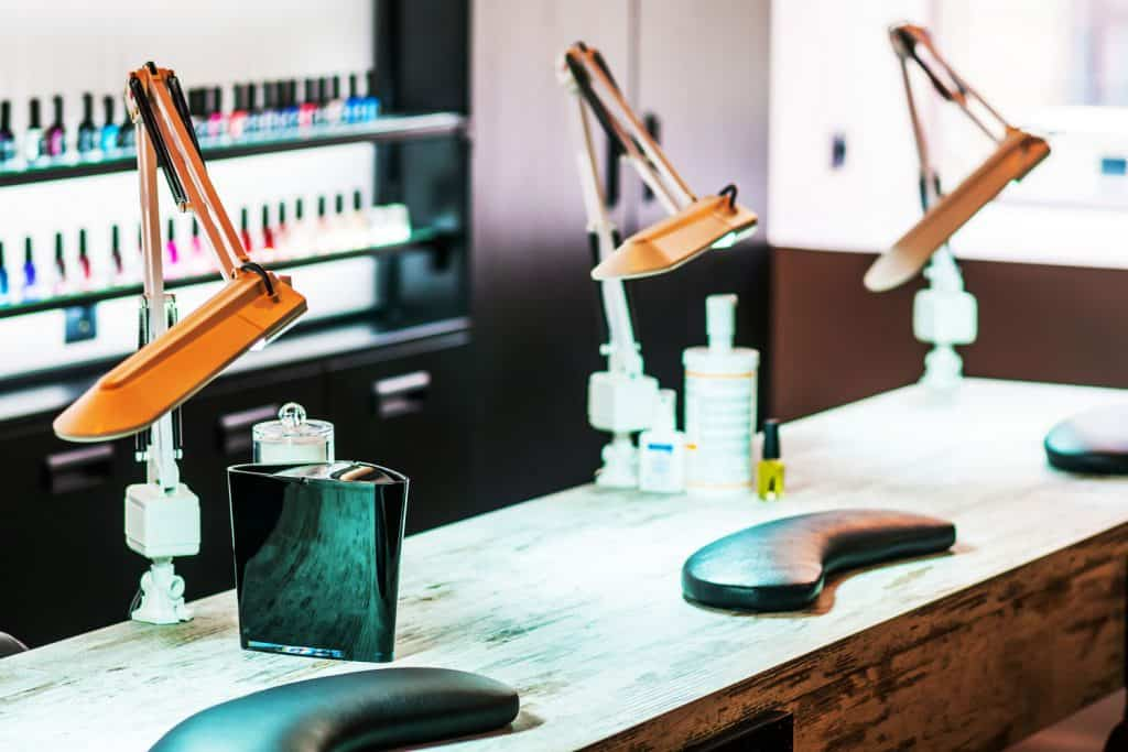 Equipment's inside a nails salon with different nail polish colors on the background
