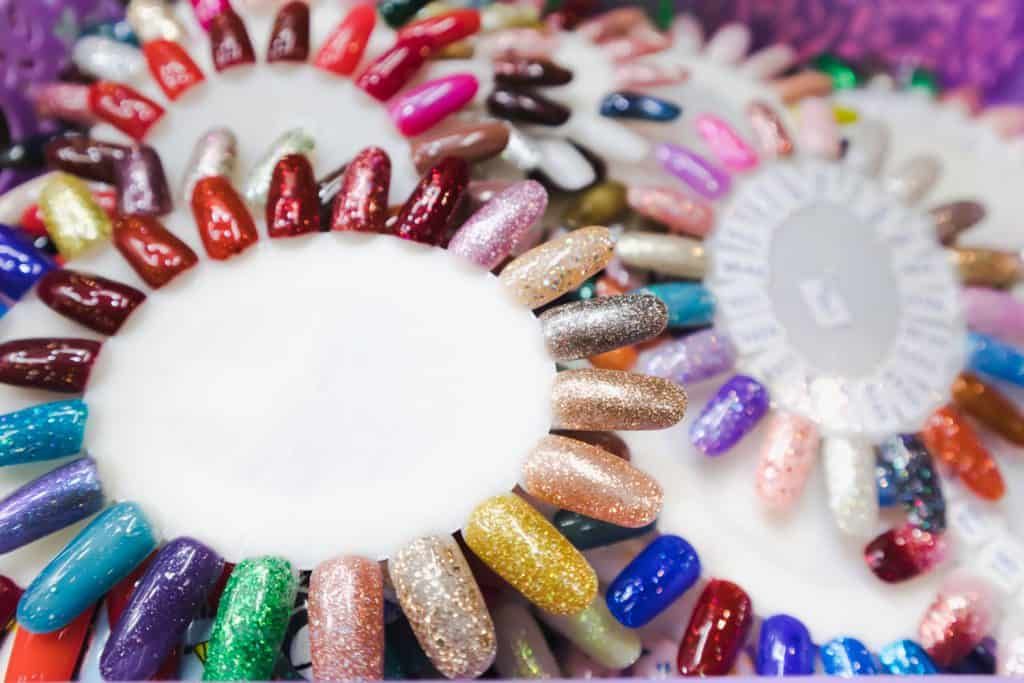 Fake Nail polish in different fashion color wheel, How Much Does It Cost To Get Fake Nails? [Breakdown By Nail Type]