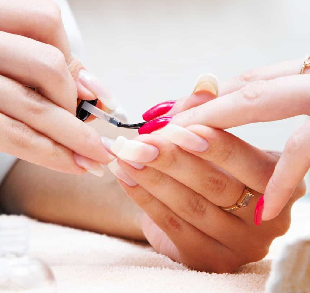 Hand getting red manicure on nails