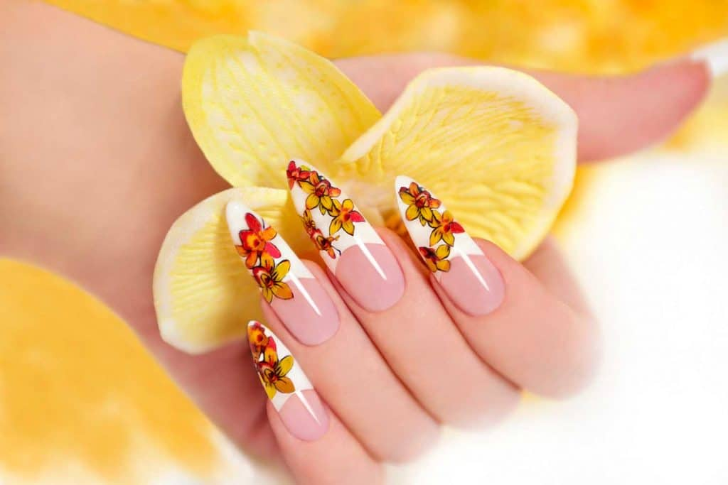 Hand with manicured nail holding yellow orchids